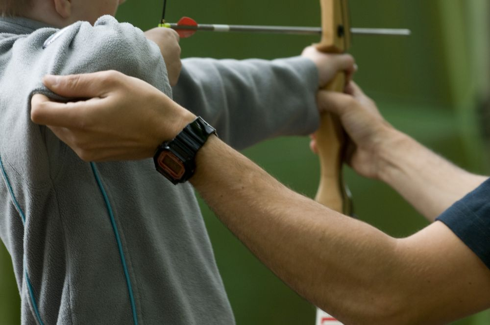 A picture of an adventure being instructed in archery