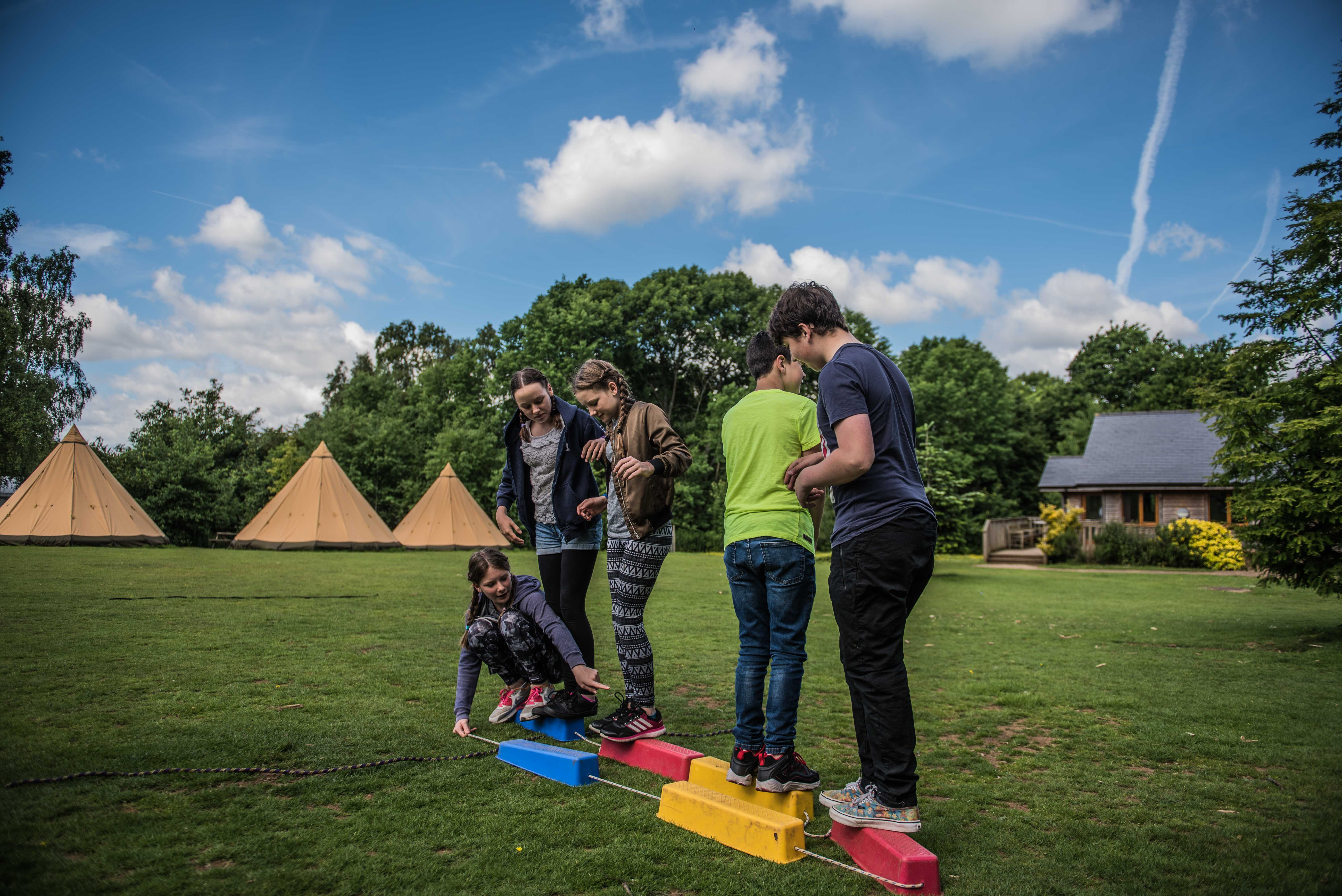 A group of summer camp residential attendees having fun during a team building game