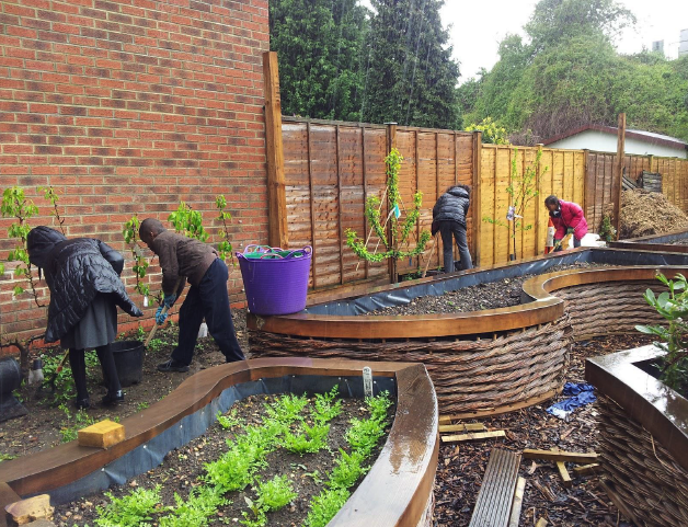 A picture of children working on Colette's secret garden as part of their outdoor learning programme in London
